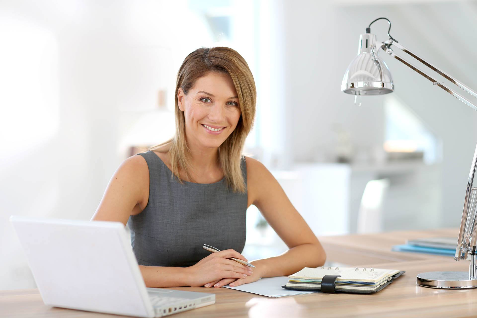 Professional dark blonde woman sitting at a desk - Virtual Office by Design
